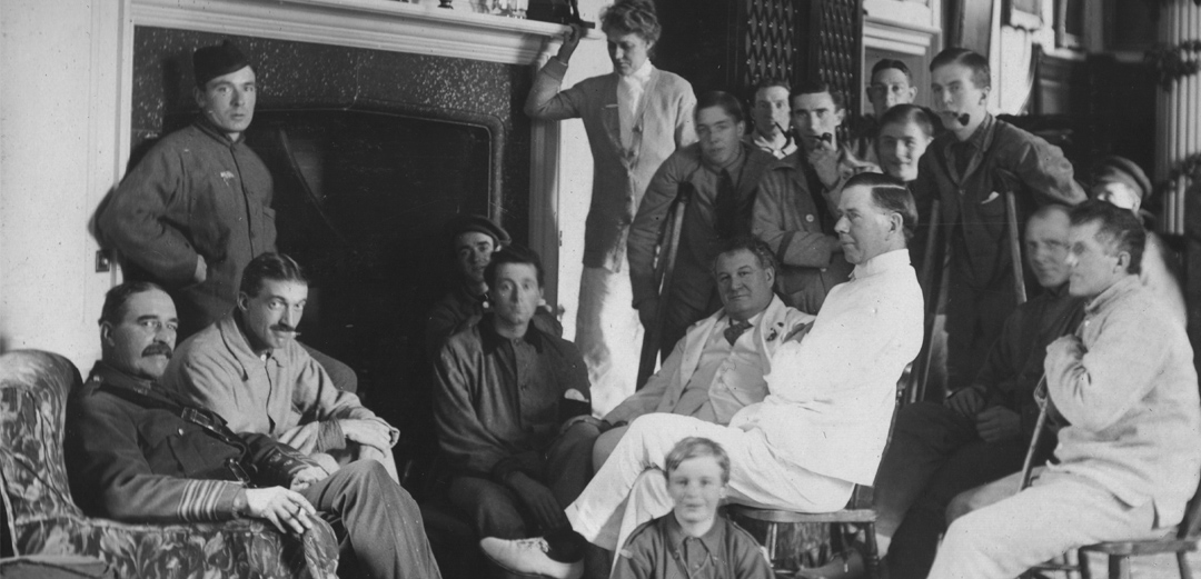 Wounded soldiers relax with their doctors and nurses in front of a fireplace